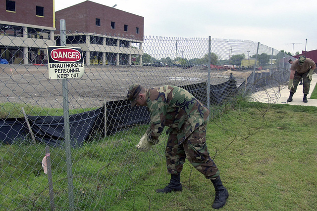 Soldiers from the 1ST Battalion, 279th Infantry, Oklahoma National Guard, fasten razor wire to the fence of a civilian-contractor construction site on the Oklahoma Air National Guard Base, Tulsa International Airport. The construction site is the future multi faceted headquarters building for the 138th Fighter Wing.  The extra measure was initiated in response to the terrorist attacks on World Trade Center and the Pentagon on September 11, 2001.The extra measure was initiated in response to the terrorist attacks on World Trade Center and the Pentagon on September 11, 2001