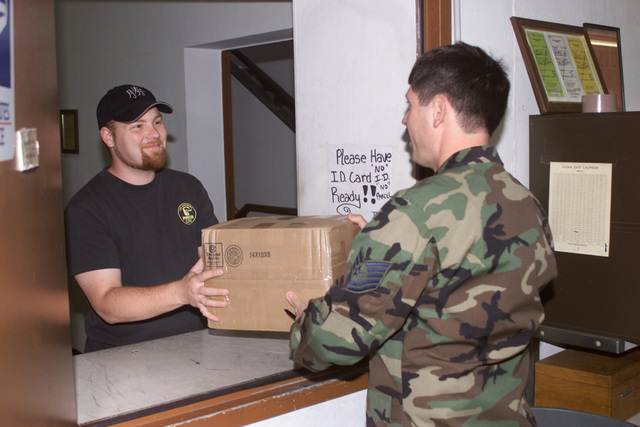 Technical Sergeant David Ledo, USAF, (right), 52nd Communications Squadron, 52nd Fighter Wing, Spangdahlem Air Base, Germany, gives mail to a customer at the Eifel West Post Office on Spangdahlem's Bitburg Annex