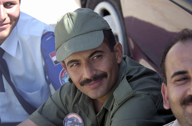 An Egyptian military member finds refuge from the mid-day sun in the shade of one of the taxis allowed entrance to Cairo West Air Base. Due to dangerous driving conditions in Egypt, US military members participating in BRIGHT STAR 01/02 must be escorted on and off base via contracted taxis. BRIGHT STAR is a multinational exercise involving more than 74,000 troops from 44 countries that enhances regional stability and military-to-military cooperation between the US, key allies, and regional partners. It prepares US Central Command to rapidly deploy and employ the forces needed to deter aggressors and, if necessary, fight and win side-by-side with our allies and regional partners