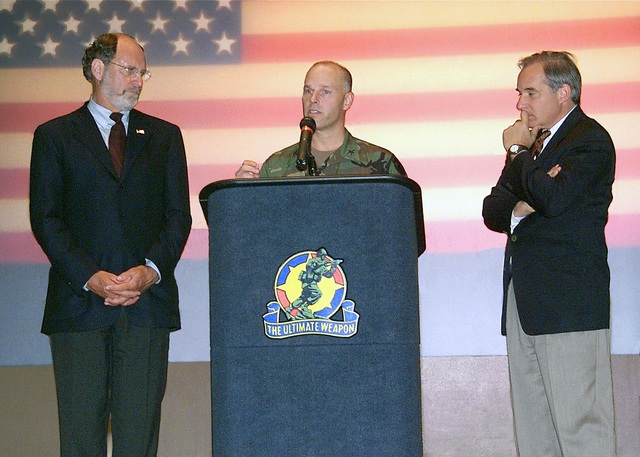 US Army Colonel (COL) David Lowry, Commander, Fort Dix, NJ, speaks at a town hall meeting following the September 11th attacks. US Senators Jon Corzine (left) and Robert Toricelli both (D-New Jersey) stand on the podium
