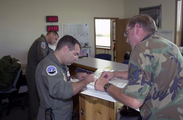 At Flight Operations, aircrew members of the 128th Air Refueling Wing (Wisconsin Air National Guard) perform final paperwork checks prior to stepping to their aircraft. They are deploying in support of Operation INFINITE JUSTICE. (Operation INFINITE JUSTICE later changed to Operation ENDURING FREEDOM)