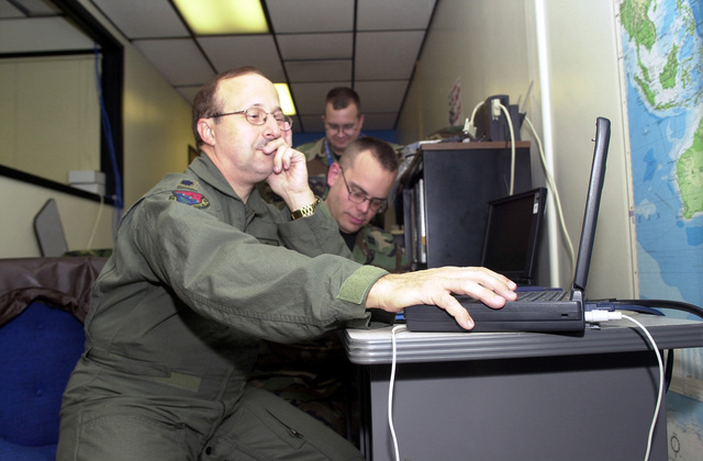 In the 193rd Special Operations Wing (SOW), Command Post, Lieutenant Colonel (LTC) Dennis Goodling, USAF, (foreground) makes final adjustments on his laptop computer to a briefing he will give later. LTC Goodling and the 193rd SOW, Pennsylvania Air National Guard, Middletown, are preparing for deployment in support of Operation ENDURING FREEDOM