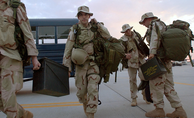 SENIOR AIRMAN (SRA) Jimmy Blevins, (center), USAF, 437th Security Forces, Charleston AFB, South Carolina, carries his gear toward an aircraft to go to an unknown forward deployed area. He is one of many Air Force personnel mobilizing for the attack on terrorism during Operation ENDURING FREEDOM