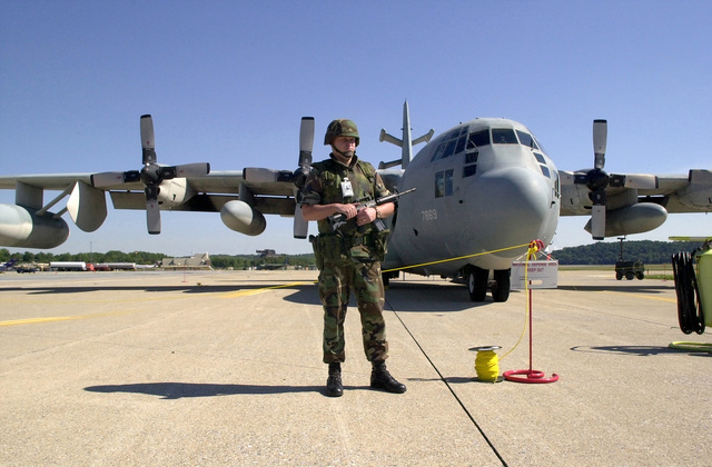 SENIOR AIRMAN (SRA) Ken Lockhart, USAF, 193rd Security Forces, 193rd Special Operations Wing (SOW), stands guard, armed with an 5.56 mm M4 Carbine and 9 mm M9 Pistol, in front of the units EC-130E (Hercules) Commando Solo aircraft