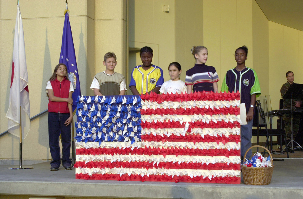 Students from the Yokota West Elementary School contribute to the Stars and Stripes Forever Memorial Service, by presenting a creatively decorated United States flag made of paper cranes, at the Sakura Shell amphitheater on Yokota Air Base, Japan