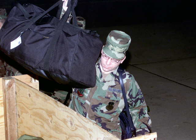 AIRMAN First Class (A1C) Roger Rose, USAF, 2nd Communications Squadron, Barksdale AFB, Louisiana, loads a crate of personal baggage for personnel deploying in support of Operation ENDURING FREEDOM