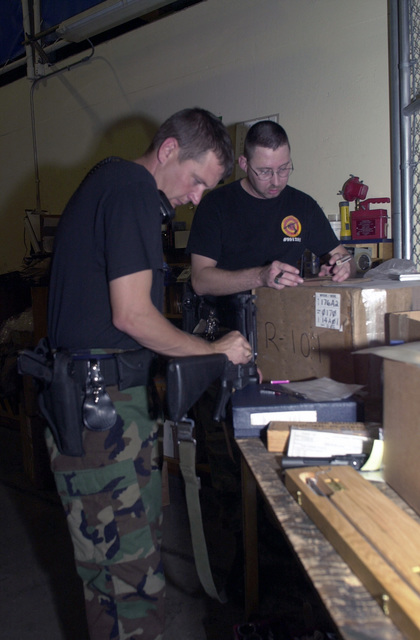 STAFF Sergeant SSGT) Michael Trump, (left), USAF, and SSGT Robert McGuirk (right), USAF, 193rd Special Operations Wing, Security Forces, check and verify weapons prior to packing them for deployment in support of Operation ENDURING FREEDOM