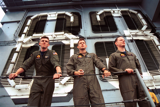 Onboard the aircraft carrier USS KITTY HAWK (CV 63), US Navy (USN) Lieutenant Junior Grade (LTJG) Sean Hays, USN LTJG Jim Lockard, and USN LTJG Max Miller, all from Electronic Attack Squadron One Three Six (VAQ-136), observe replenishment operations from an upper deck position