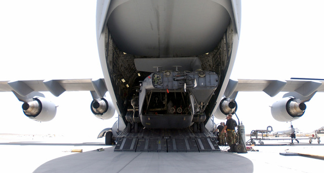 A MH-53J/M Pave Low, 20th Special Operations Squadron (SOS), Hurlburt Field, Florida, is downloaded from a C-17A Globemaster III at an unknown forward deployed location. The tasking of this equipment is part of the mobilization for the attack on terrorism during Operation ENDURING FREEDOM