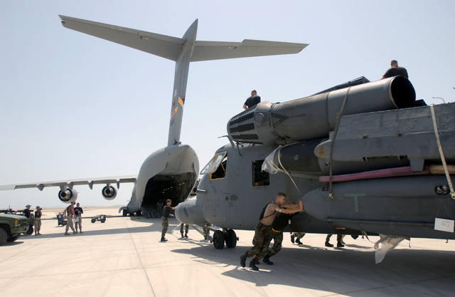 A MH-53J/M Pave Low, 20th Special Operations Squadron (SOS), Hurlburt Field, Florida, is taken off a C-17A Globemaster III, at an unknown forward deployed location. The tasking of this equipment is part of the mobilization for the attack on terrorism during Operation ENDURING FREEDOM