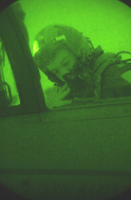 As seen through a night vision lens, Captain Doug Bartels, USAF, 494th Fighter Squadron, RAF Lakenheath, UK, goes over a final check as he prepares for take off in an F-15E Strike Eagle. Due to the extended periods of darkness during the winter months, the base shifted to night operations as of September 10th and will continue through March. F-15E Strike Eagles launch from RAF Lakenheath in the early evening and generally return around 1130PM (2330)