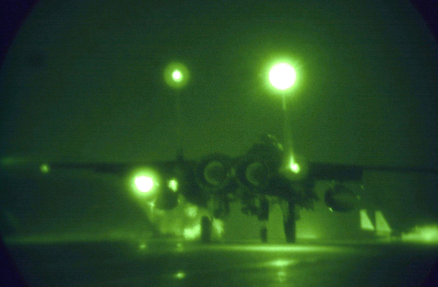 As seen through a night vision lens the F-15E Strike Eagle piloted by Captain Doug Bartels, USAF, and Captain Mark Ciero, USAF, Weapons System Operator, 494th Fighter Squadron, RAF Lakenheath, UK, taxies away toward the runway for take off. Due to the extended periods of darkness during the winter months, the base shifted to night operations as of September 10th and will continue through March. F-15E Strike Eagles launch from RAF Lakenheath in the early evening and generally return around 1130 PM (2330)