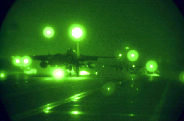As seen through a night vision lens, two F-15E Strike Eagles from the 494th Fighter Squadron, RAF Lakenheath, UK, taxi down runway for take off. Due to the extended periods of darkness during the winter months, the base shifted to night operations as of September 10th and will continue through March. F-15E Strike Eagles launch from RAF Lakenheath in the early evening and generally return around 1130PM (2330)