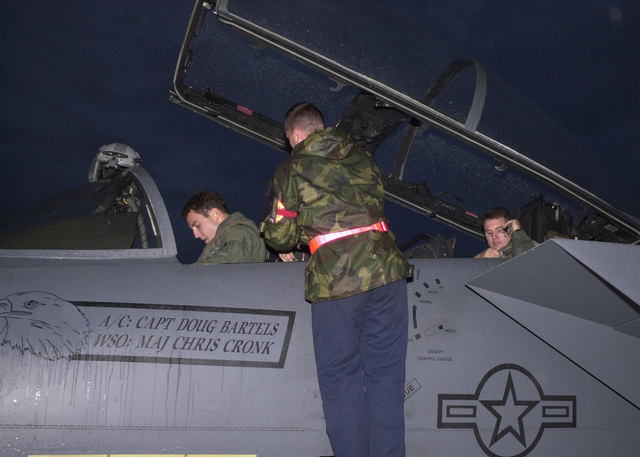 """Captain Doug Bartels, USAF, (left), pilot, and Captain Mark Ciero, USAF, (right), Weapons System Operator, 494th Fighter Squadron, RAF Lakenheath, UK, strap into an F-15E Strike Eagle prior to """"Night Flight"""". The crewchief will double-check all straps before the canopy closes. Due to the extended periods of darkness during the winter months, the base shifted to night operations as of September 10th and will continue through March. F-15E Strike Eagles launch from RAF Lakenheath in the early evening and generally return around 1130PM (2330)"""