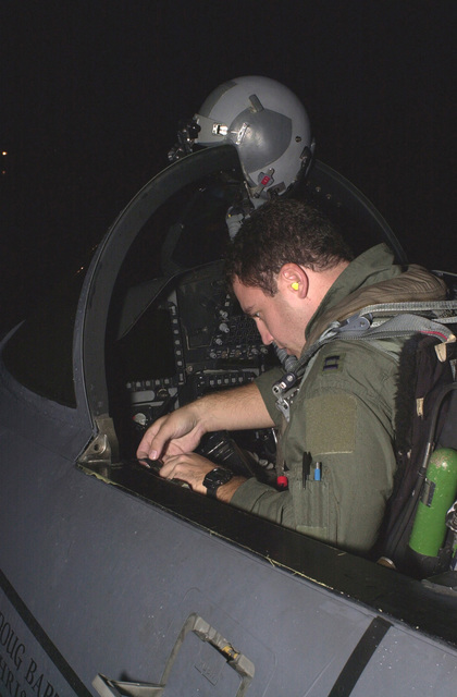 Captain Doug Bartels, USAF, pilot, 494th Fighter Squadron, RAF Lakenheath, UK, runs through a preflight checklist prior to night operations. Due to the extended periods of darkness during the winter months, the base shifted to night operations on September 10th and will continue through March. F-15E Strike Eagles launch from RAF Lakenheath in the early evening and generally return around 1130PM (2330)