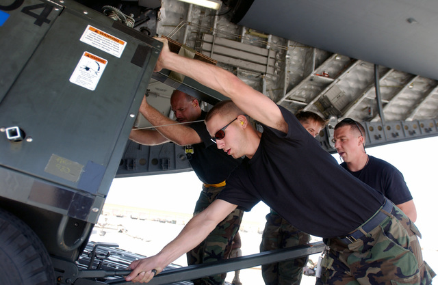 SENIOR AIRMAN (SRA) Robert Furr, USAF, (foreground), 16th Helicopter Generation Squadron (HGS), Hurlburt Field, Florida, helps unload a generator off a C-17A Globemaster III, at a forward location in support of Operation ENDURING FREEDOM