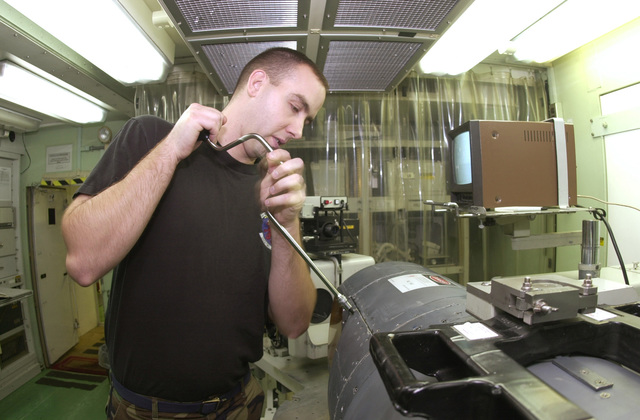 During a routine maintenance inspection, STAFF Sergeant Corey Dutton, USAF, an Aviation Sensors Journeyman, 31st Maintenance Squadron, 31st Fighter Wing, Aviano Air Base, Italy, removes the shroud window covering the video lens in the targeting pod