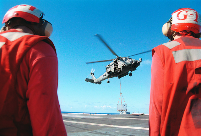 US Navy (USN) Aviation Ordnancemen (AO) from Weapons Department, G-1 Division watch as a US Navy (USN) SH-60F Seahawk helicopter from Helicopter Anti-Submarine squadron One Four (HS-14) lifts a cargo cage from the flight deck of the aircraft carrier USS KITTY HAWK (CV 63), during Vertical Replenishment (VERTREP), operations
