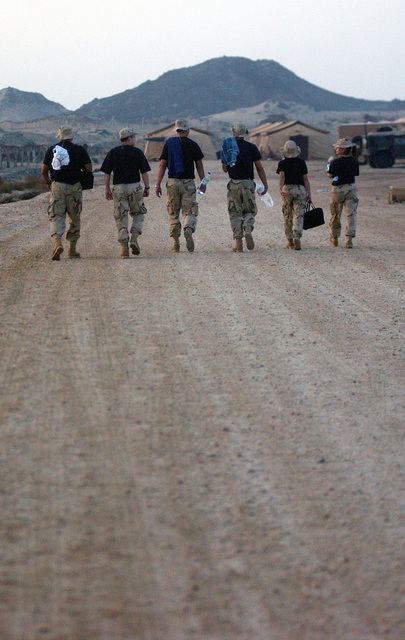 Six Air Force members from the 59th Medical Wing, Lackland AFB, Texas, walk toward the showers immediately after arriving at an undisclosed forward deployed location. They deployed in support of Operation ENDURING FREEDOM
