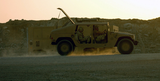 US Air Force (USAF) personnel drive their M1038 High-Mobility Multi Purpose Wheeled Vehicle (HMMWV) through the perimeter at an undisclosed forward-deployed location. They are deployed along with many other personnel throughout the USAF to support Operation ENDURING FREEDOM