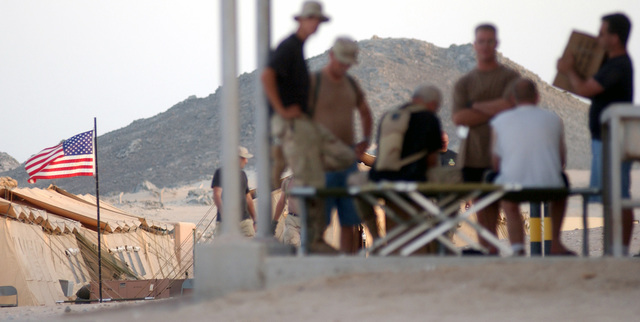 With Old Glory waving, Air Force personnel take a break after a sixteen-hour plus day setting up tents at their bare base. They are at an undisclosed forward location in support of Operation ENDURING FREEDOM