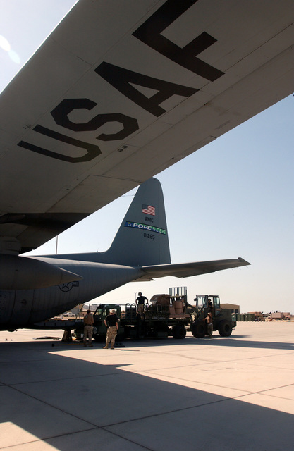621st Air Mobility Operations Group (AMOG) Tanker Airlift Control Element (TALCE), McGuire AFB, New Jersey, use a combination of a 25K-loader and a 10K John Deere 644E-H forklift to unload cargo off a C-130 Hercules, 43rd Airlift Wing, Pope AFB, North Carolina during Operation ENDURING FREEDOM