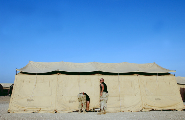 SENIOR AIRMAN (SRA) Robert Irvine, USAF, and STAFF Sergeant (SSGT) Martin Grant, USAF, 2nd Civil Engineering Squadron (CES), Barksdale AFB, Louisiana, help put up and secure TEMPER (Tent, Extendable, Modular, Personnel) tents in 100 degree weather at an undisclosed forward deployed location in support of Operation ENDURING FREEDOM