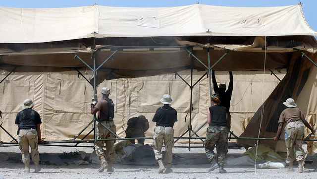 Several deployed Air Force members join to set up TEMPER (Tent, Extendable, Modular, Personnel) tents in 100 degree weather at an undisclosed forward deployed location. They and others in this camp are setting up a Tent City to house troops deployed in support of Operation ENDURING FREEDOM