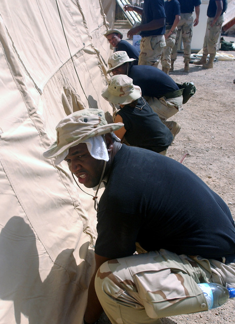 STAFF Sergeant (SSGT) Mike Edwards, USAF, 59th Medical Wing, Lackland, Texas, along with co-workers picks up and adjusts the position of an TEMPER (Tent, Extendable, Modular, Personnel) tent in 100 degree weather at an undisclosed forward deployed location in support of Operation ENDURING FREEDOM