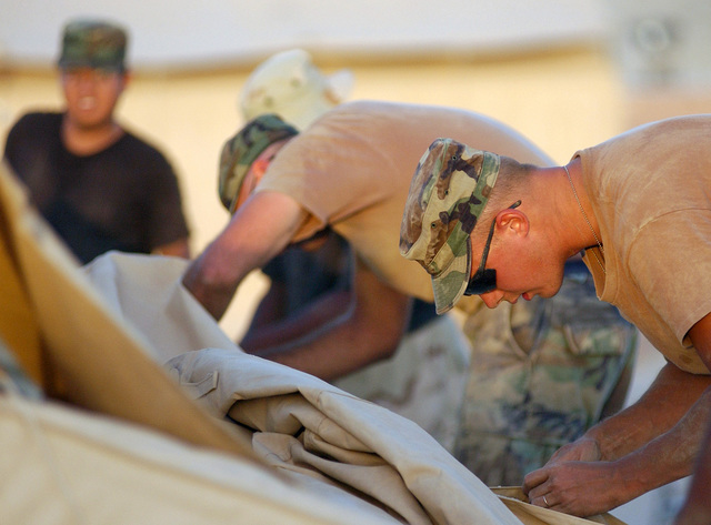 STAFF Sergeant (SSGT) Ronald Hall, USAF, 7th Civil Engineering Squadron, Dyess, Texas, part of the team assembling TEMPER (Tent, Extendable, Modular, Personnel) tents in 100 degree weather at an undisclosed forward deployed location in support of Operation ENDURING FREEDOM