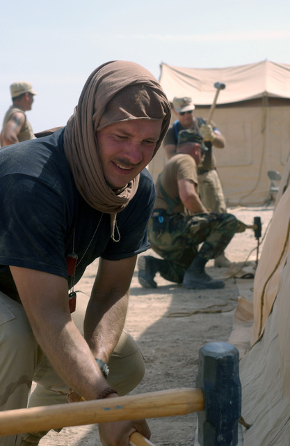Technical Sergeant (TSGT) David Miller, USAF, 7th Supply Squadron, Dyess AFB, Texas, assists in hammering down pegs to an TEMPER (Tent, Extendable, Modular, Personnel) tent in 100 degree weather in an undisclosed forward deployed location. He and others in the camp are setting up Tent City in support of Operation ENDURING FREEDOM