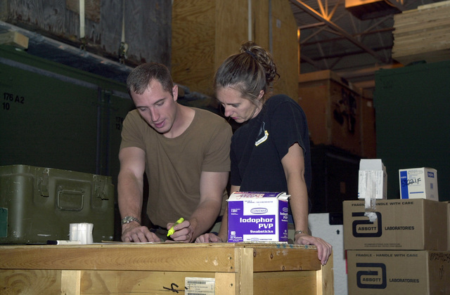 Technical Sergeant (TSGT) David Stine, (left), USAF, and MASTER Sergeant (MSGT) Lori Zimmerman, (right), USAF, 193rd Special Operations Wing (SOW) Medical Squadron inspect items they are packing in preparation for deployment in support of Operation ENDURING FREEDOM