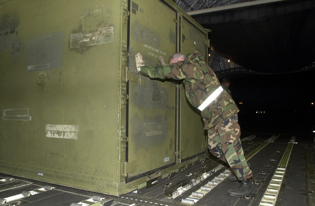 MASTER Sergeant (MSGT) Mike Whitman, USAF, 193rd Special Operations Wing (SOW), gives a little extra push to align an Internal Airlift or Helicopter Slingable Container Unit (ISU-90) as it is loaded onboard a C-17A Globemaster III. The equipment loaded is from the 193rd Special Operations Wing (SOW), Pennsylvania Air National Guard unit deploying in support of Operation ENDURING FREEDOM
