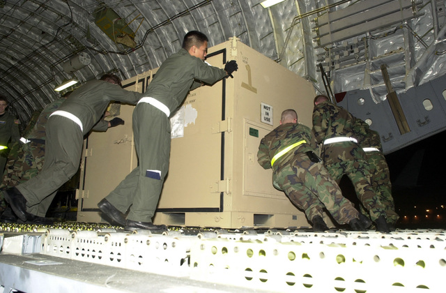 The load crew puts some extra muscle as they push an Internal Airlift or Helicopter Slingable Container Unit (ISU-60) onto a C-17A Globemaster III. The equipment loaded is from the 193rd Special Operations Wing (SOW), Pennsylvania Air National Guard unit deploying in support of Operation ENDURING FREEDOM