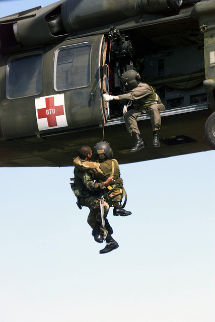 A crewmember aboard a US Army UH-60 Black Hawk medivac helicopter, prepares to assist soldiers from the 507th Medical Company, 1ST Medical Brigade, 13th Corps Support Command, aboard the aircraft, as they practice hoisting skills during an Aeromedical Evacuation exercise