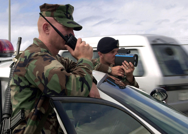 US Air Force (USAF) SENIOR AIRMAN (SRA) Joel Meyer, 18th Security Forces Squadron, uses a radar gun to clock a motorist as US Marine Corps (USMC) Sergeant (SGT) Willis Jeffrey, 3rd Marine Division, Light Armored Reconnaissance Company, relay information on a hand held radio. USAF and USMC Security Personnel are conducting cross training at Kadena AB, Japan, during Operation ENDURING FREEDOM