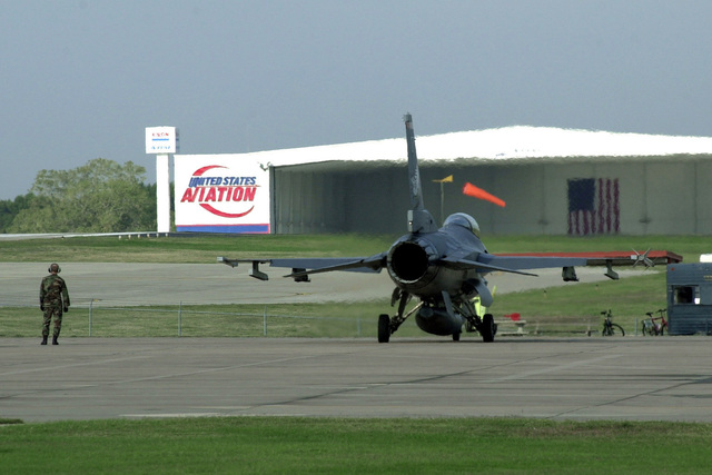 An F-16C Fighting Falcon, 138th Fighter Wing (FW), Oklahoma Air National Guard Base, Tulsa goes through pre-flight checks before entering the runway at Tulsa International Airport. Like many Air National Guard units, the civilian airport and the 138th Fighter Wing share the runway. United States Aviation sits in the background displaying an American flag in their hangar