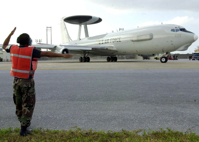 US Air Force (USAF) AIRMAN First Class (A1C) Bryan Campbell, Crew CHIEF, 961st Airborne Air Control Squadron, marshals a US Air Force (USAF) E-3C Sentry Airborne Warning and Control System (AWACS) aircraft onto the flight line at Kadena AB, Japan, during Operation ENDURING FREEDOM