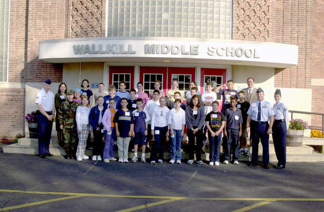 Flanking Wallkill Middle School seventh graders, Teachers & members of the 105th Airlift Wing pose for group photo. On the left side are STAFF Sergeant Ed Gorman, Teacher Mrs. Lori Hughes, and Second Lieutenant Kimberly Cardona-Smith, Commander of the 105th Communications Squadron. On the right (left to right) Principal Mr. Victor Livocorri, Technical Sergeant (TSGT) Michael Antinucci, and TSGT Kathy Sileno. The students gathered food and pack it into boxes as donations for 105th Air Wing, Air National Guard, members serving at Ground Zero at the World Trade Center collapse. The collapse due to terrorist flying two large passenger aircraft into the buildings; killing all in the planes and...