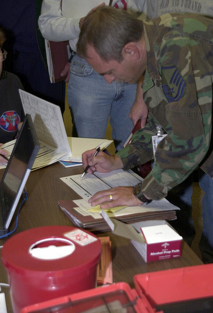 A MASTER Sergeant from the 128th Air Refueling Wing (ARW), Wisconsin Air National Guard, Medical Squadron, fills out paperwork for immunizations provided for 128th ARW members during out-processing in support of Operation ENDURING FREEDOM