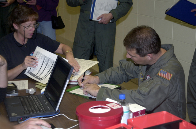 A member of the 128th Air Refueling Wing (ARW), Wisconsin Air National Guard, fills out paperwork as he and others prepare to deploy in support of Operation ENDURING FREEDOM