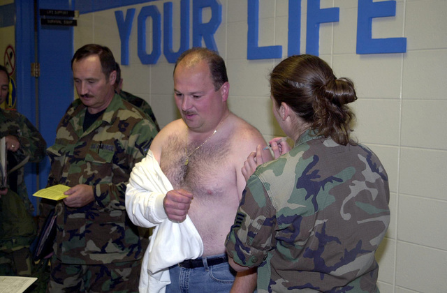 A member of the 128th Air Refueling Wing (ARW), Wisconsin Air National Guard, receives immunization shots as he and others prepare to deploy to an undisclosed location in support of Operation ENDURING FREEDOM
