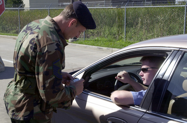 MASTER Sergeant (MSGT) Weber, (left), USAF, 128th Air Refueling Wing (ARW), Wisconsin Air National Guard, performs ID checks and vehicle inspections at the Main gate. Intensified security measures are in place due to Operation ENDURING FREEDOM