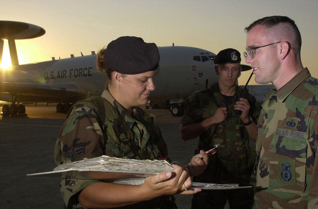 US Air Force (USAF) AIRMAN First Class (A1C) Shelly Byers (left), 325th Security Forces Squadron (SFS), checks the flight line badge of a unidentified USAF AIRMAN attempting to gain access to the area as USAF STAFF Sergeant (SSGT) John Duly (center), 175th Fighter Wing (FW), looks on. Both A1C Byers and SSGT Duly are deployed at Incirlik Air Base (AB), Turkey, in support of Operation NORTHERN WATCH. A USAF E-3C Sentry Airborne Early Warning and Control System (AWACS) aircraft is parked in the background