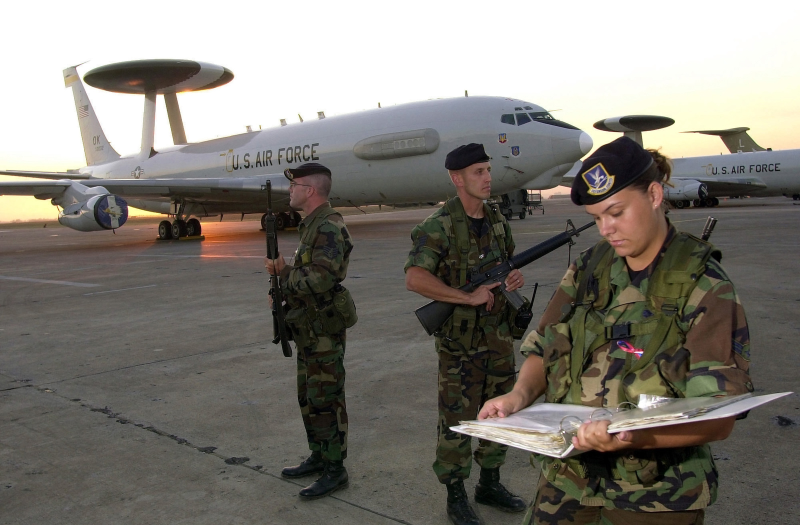 US Air Force (USAF) Security Police (SP) armed with 5.56mm M16A2 rifles guard USAF E-3C Sentry Airborne Early Warning and Control System (AWACS) aircraft, on the flight line at Incirlik Air Base (AB), Turkey, while deployed in support of Operation NORTHERN WATCH. Pictured left-to-right, USAF STAFF Sergeant (SSGT) John Duly, 175th Fighter Wing (FW); USAF SSGT Paul Evans, 172nd FW; and USAF AIRMAN First Class (A1C) Shelly Byers, 325th FW