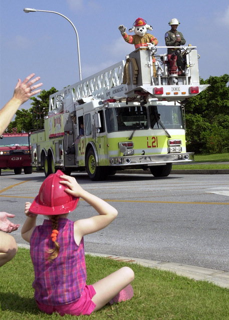 """Kicking off Fire Prevention Week """"Sparky"""" travels onboard a KME Aerialcat 4 door cab forward Aerial Tower leading a Fire Truck parade through Kadena base housing areas. Sparky waves at Megan McClain, 5, daughter of Michele and Mike McClain, Department of Defense Dependents (DoDD) schoolteachers"""