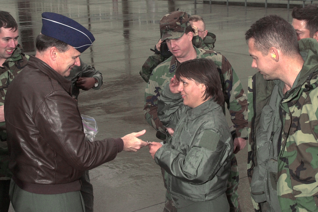US Air Forces in Europe commander, General (GEN) Gregory S. Martin, USAF, presents a USAFE coin to a C-17 Globemaster III crewmember, after completing humanitarian airdrops in Afghanistan in support of Operation ENDURING FREEDOM