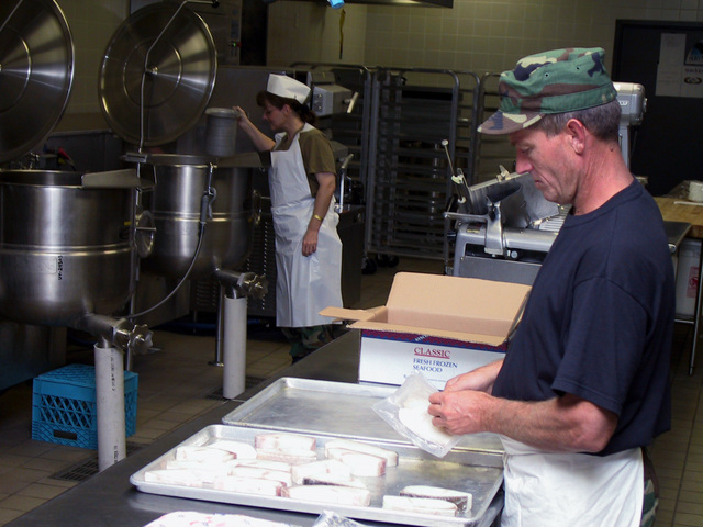 "Traditional Guardsmen, SENIOR AIRMAN Darrell Webb, USAF, (right) and STAFF Sergeant Denise Officer, USAF, of the 151st Services Flight, Utah Air National Guard, Salt Lake City, prepare ""Midnight Chow"" for personnel activated in support of Operation NOBLE EAGLE. NOBLE EAGLE is a partial mobilization of the reserves for homeland defense and civil support missions in response to the terrorist attacks on September 11, 2001 at the New York World Trade Center and the Pentagon"