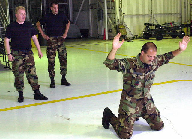 In preparation for Operation ENDURING FREEDOM, Technical Sergeant Jason McAfferty, USAF, (with hands up) of the 138th Communication Flight, follows the orders of STAFF Sergeant Scott Elliott, USAF, (left) of the 138th Mission Support Flight. During a Security Force augmentee training class with the 138th Fighter Wing, Tulsa Air National Guard, Tulsa Oklahoma. ENDURING FREEDOM is in support of the Global War on Terrorism (GWOT), fighting terrorism abroad