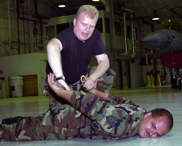 In preparation for Operation ENDURING FREEDOM, Technical Sergeant Jason McAfferty, USAF, of the 138th Communications Flight, submits as STAFF Sergeant Scott Elliott, USAF, of the 138th Mission Support Flight detains and handcuffs him. This is part of the training during a Security Force augmentee class held at the 138th Fighter Wing, Tulsa Air National Guard, Tulsa Oklahoma. ENDURING FREEDOM is in support of the Global War on Terrorism (GWOT), fighting terrorism abroad